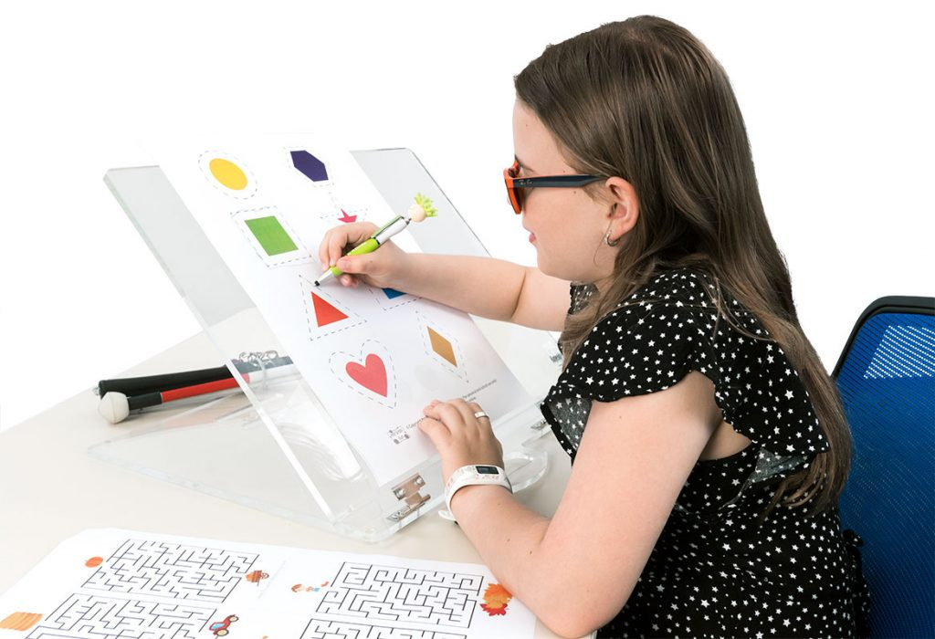 Young girl leaning to draw shapes